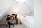 A bedroom in white in an attic with a bed, an antique wooden chair and a bedside table
