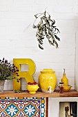 Yellow kitchen utensils such as vinegar pot and oil bottle on wooden shelf in Mediterranean kitchen