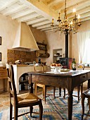 Kitchen-dining room with old oak table and farmhouse chairs in Tuscan country house