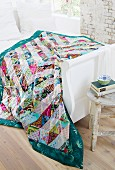 Patchwork blanket on white, wooden bed