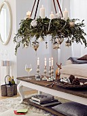 A hanging advent wreath made from olive twigs with silver balls and white candles