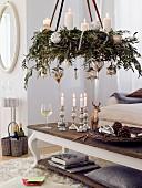 Hängender Adventskranz aus Olivenzweigen mit silbernen Kugeln und weißen Kerzen