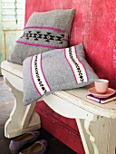 Scatter cushions with embroidered covers on wooden bench