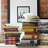 Books stacked on surface against brick wall