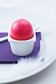 A pink Easter egg in a simple egg cup on a purple place mat