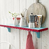 Kitchen utensils on blue shelf with red decorative trim