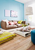 Colourful scatter cushions on sofa and floor and low coffee table with vases of flowers on tray