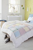 Bed with patchwork quilt in simple bedroom