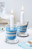 White burning candles in glasses of blue and white sand