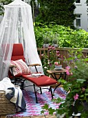 Balcony with red lounger, mosquito net, side table and flowers