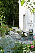 Small table, chairs and bench against house facade in garden