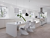 A spacious modern kitchen in white with a long dining and seating area