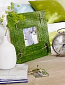 Moss-green, woven raffia picture frame decorated with parcel string