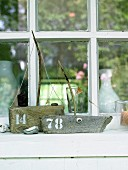 Homemade sailing boats made of driftwood as decoration on a windowsill