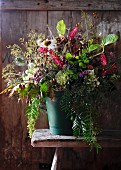 Autumnal bouquet in vase on wooden stool
