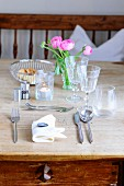 A place setting with cutlery and glasses on a rustic wooden table