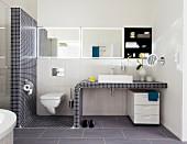 Wachtisch mit Mosaikfliesen und Toilette im Badezimmer