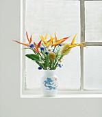 Strauss aus langstieligen Blumen - Helikonien und Ingwerblüten - in einer Vase am Fenster