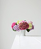 Colourful hydrangeas in vase on white table