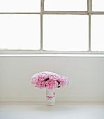 Bouquet of peonies in vase on floor