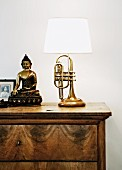 Lamp upcycled from old trumpet & Buddha figurine on chest of drawers