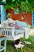 Dog lying in front of garden swing with seat cushion & scatter cushions in garden