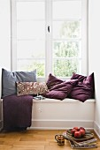 Scatter cushions on window seat in niche