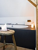 Fitted designer bathtub and rustic wooden stool