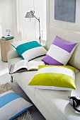 Scatter cushions with wide, brightly-coloured stripes on sofa