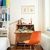 A wooden bureau in the corner of a room next to a modern metal shelf filled with office supplies