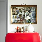Gilt-framed photo collage above red, retro fridge