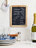 Notes on a blackboard, a stack of crockery and a bottle of sparkling wine a student kitchen