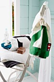 Towels & bag of toiletries on folding chair in Scandinavian guest house