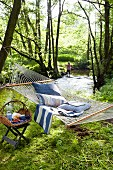 Cushions in hammock and picnic basket on stool in woodland
