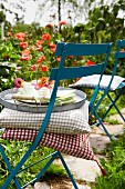 Cushions & tray on folding chair in summery garden