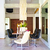 Dining room with high ceiling, dining table, leather swivel chairs & decorative pendant lamp