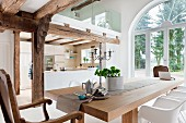 Open-plan interior with wood-beamed ceiling, kitchen, dining area & mezzanine