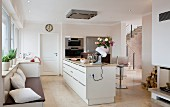 Open-plan kitchen with island counter, bench & fireplace
