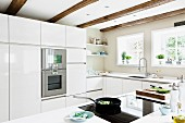 White fitted kitchen with glossy fronts