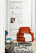 Brown leather armchair in front of white shelving on wall