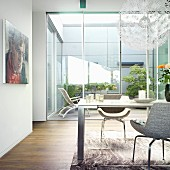 A dining table in a modern living room with a view of an atrium