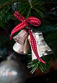 Silver bells with a red bow on a Christmas tree
