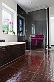 Bathroom with shower behind glass partition, bathtub & crocodile-skin-effect floor tiles