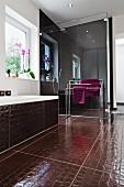 Bathroom with shower behind glass partition, bathtub & crocodile-skin-effect floor tiles