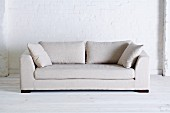 White sofa against white-painted brick wall