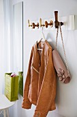 Leather jacket & handbag hanging on DIY coat rack with doorknobs as hooks