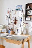 A writing desk with a homemade noteboard made from a wooden picture frame