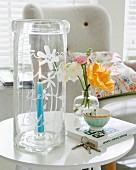 A tall, glass, hand-engraved lantern on a side table