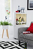 Armchair & drinks cabinet in living room with contrasting red, grey and white decor