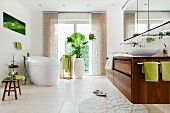 A spacious bathroom in white with a free-standing bathtub, a wooden vanity unit and touches of green